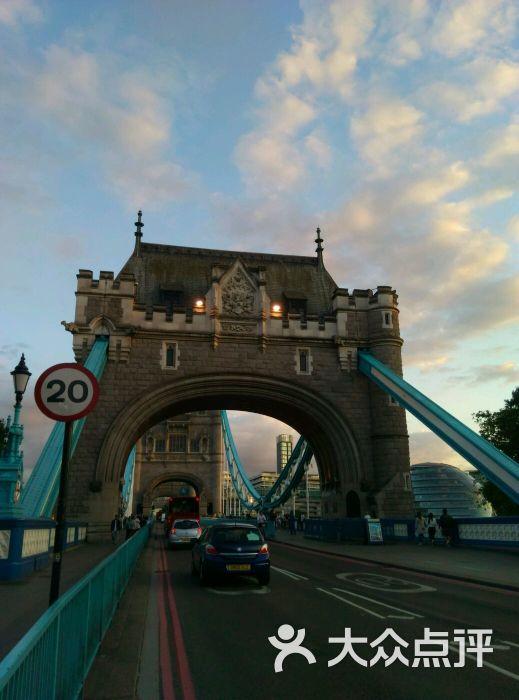 伦敦塔桥是伦敦的地标建筑之一,也是伦敦的象征。 伦敦塔桥的设计颇为合理,在世界桥梁建筑业中有口皆碑。两岸两座用花岗石和钢铁建成的高塔,高约60米,分上下两层。上层支撑着两岸的塔,下层桥面可让行人通过,也可供车辆穿行。如果巨轮鸣笛而来,下层桥面能够自动往两边翘起,此时行人可改道从上层通过。桥内设有商店、酒吧,即使在雨雪天,行人也能在桥中购物、聊天或凭栏眺望两岸风光。 从外表来看,塔桥的两端是维多利亚时代的砖石 远观伦敦塔桥塔,但实际上塔身的结构主要是钢铁的。里面装有用来开合各重1000吨桥梁的水力机械。塔桥